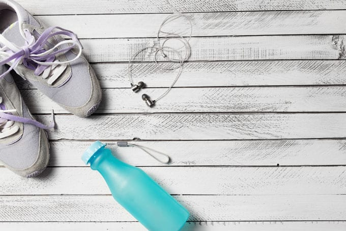 Overhead shot of workout shoes, water bottle, and ear buds.