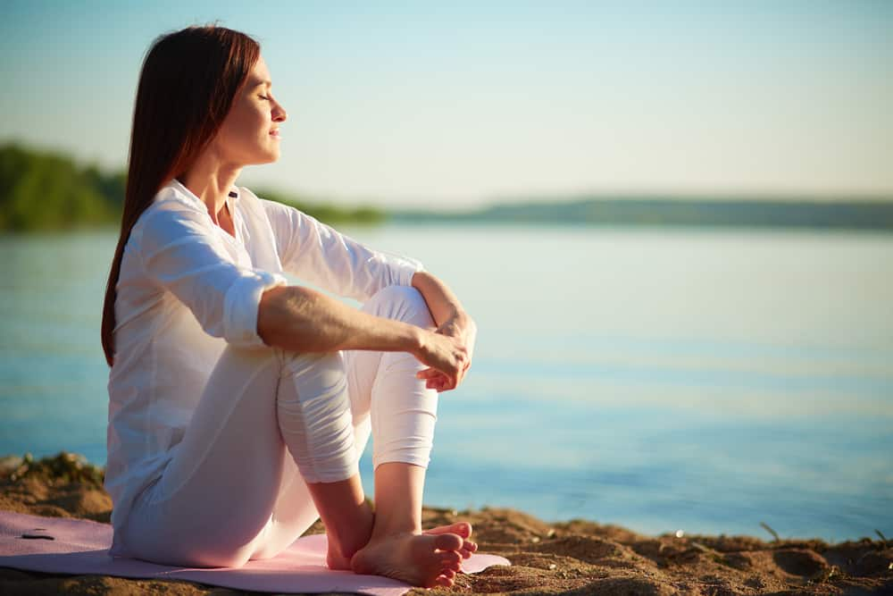 Woman sitting on a beach relaxed and meditating.