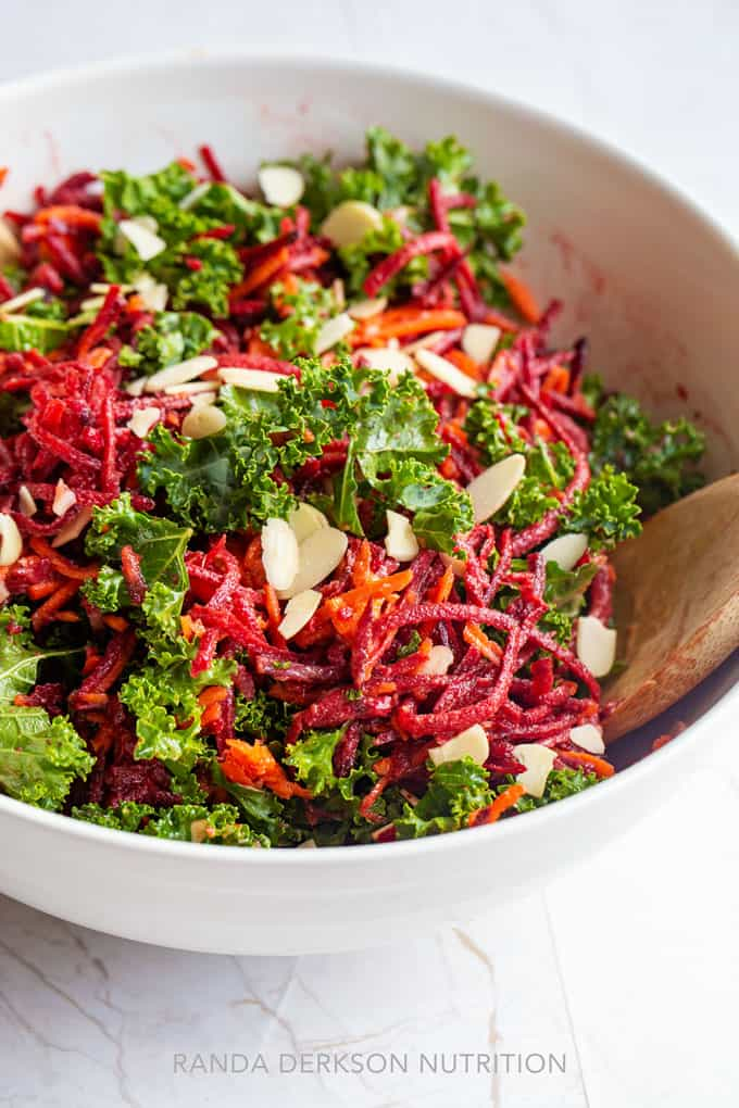 shredded beet, carrots, and kale in a white bowl tossed with vinaigrette and almonds