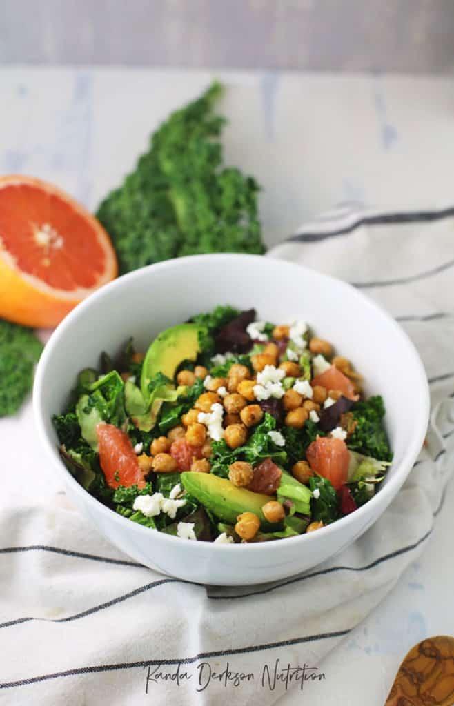 Salad bowl with chickpeas, avocado, kale, romaine, grapefruit, and feta with a grapefruit dressing