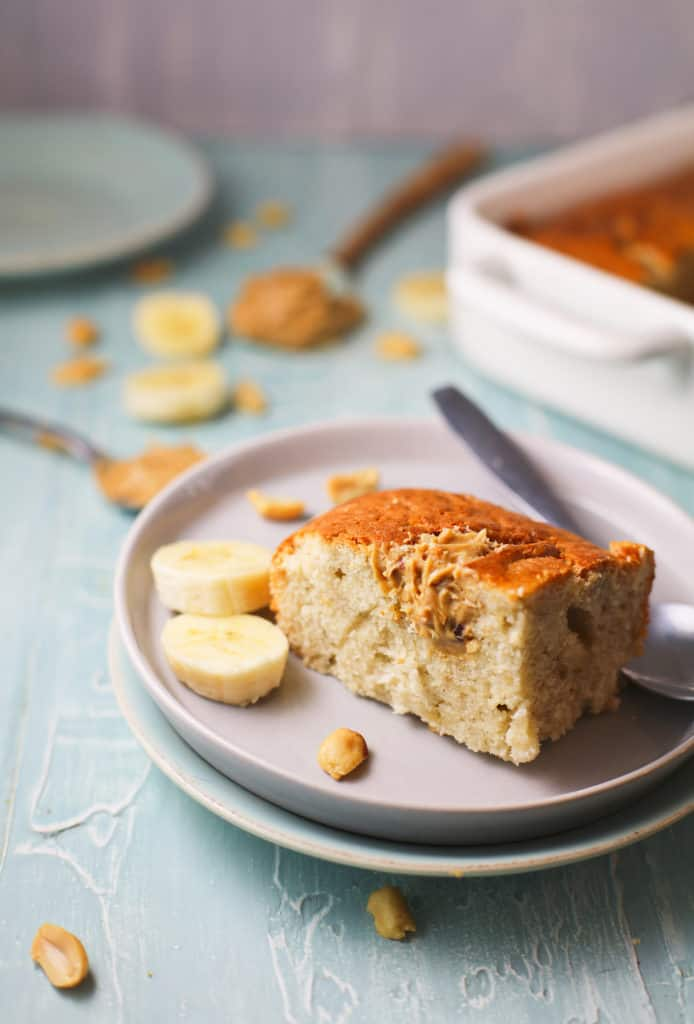 slice of banana bread on a white plate with a dollop of peanut butter swirled on top