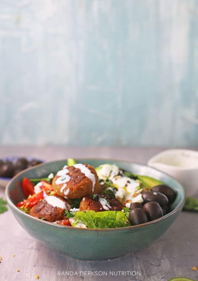plant based salad in a blue bowl with a greek yogurt tahini dressing