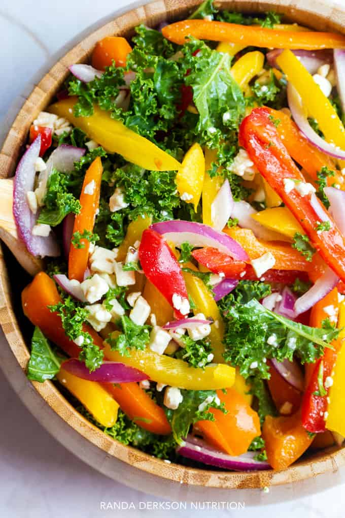looking down on a wooden bowl with kale, bell peppers, feta cheese, and purple onion tossed together in a sesame rice vinaigrette