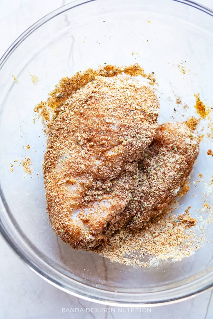 chicken being dredged in a bowl of almond flour and fajita spices