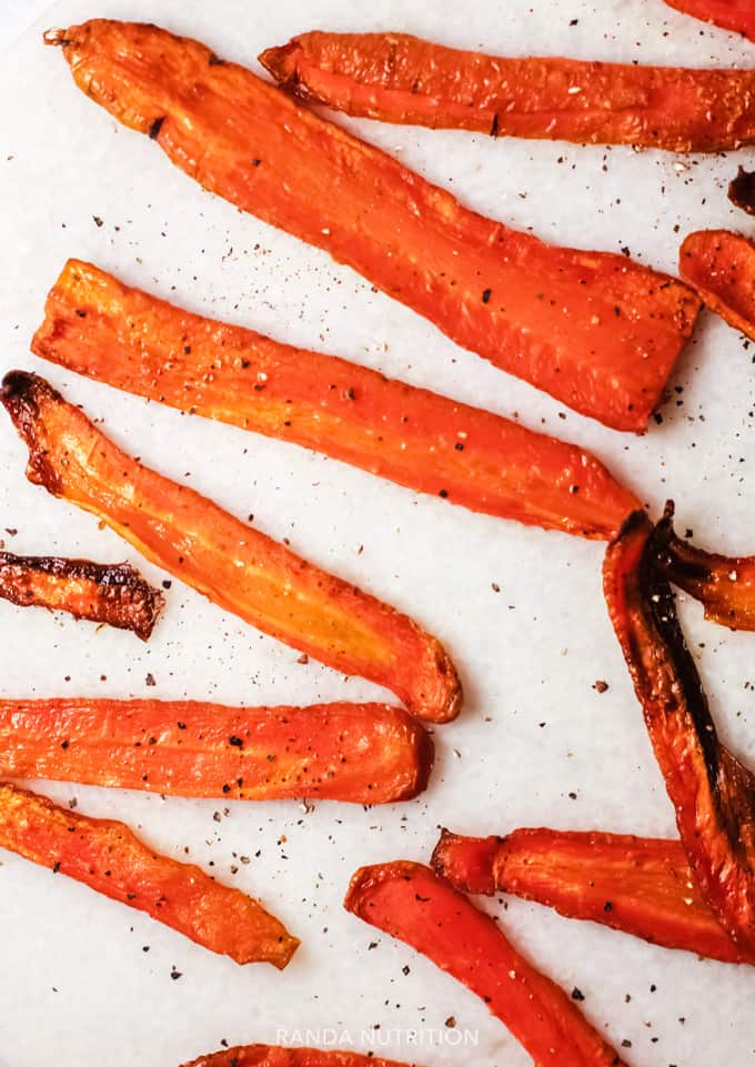 baked carrot fries on a white background