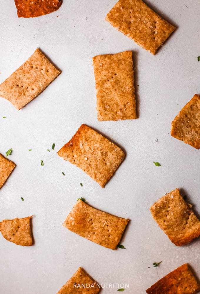 baked gluten free crackers on a counter with herbs