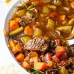 hearty beef and vegetable soup in a white bowl with crackers.