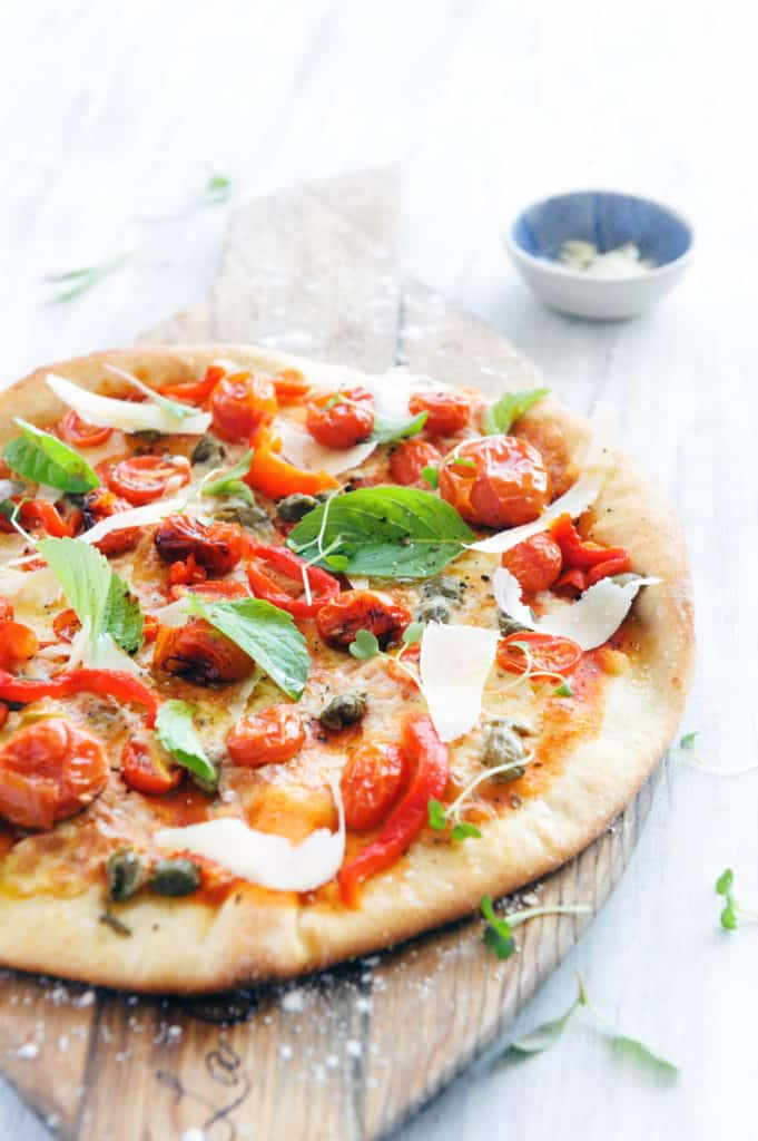 roasted tomatoes and basil on top of a healthy pizza crust