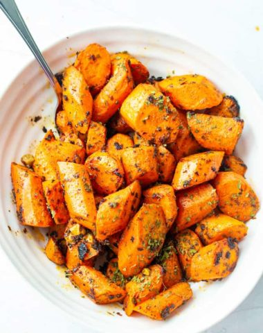 overhead view of crunch oven roasted carrots with a serving spoon as a side dish