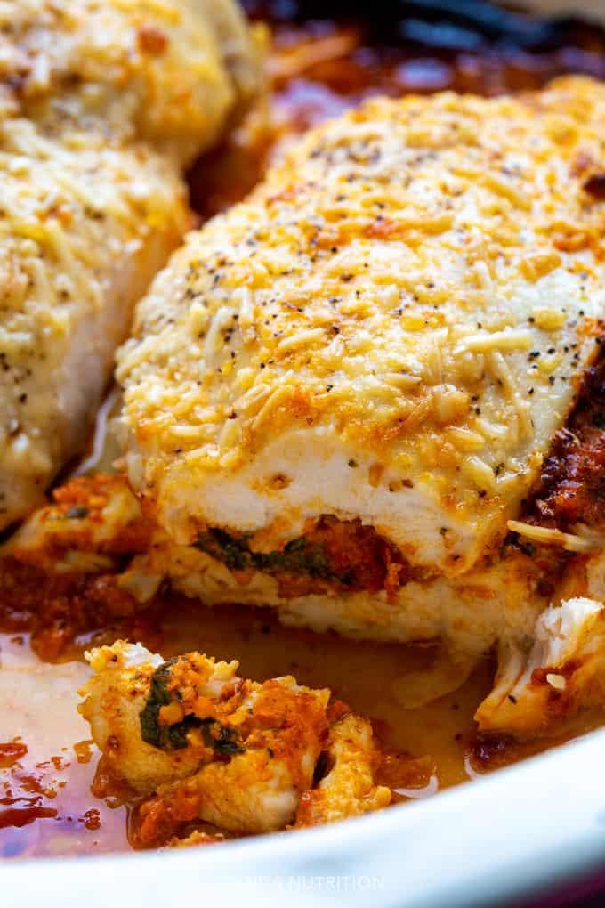Cheesy stuffed chicken with romesco sauce, mozzarella, and spinach sliced into