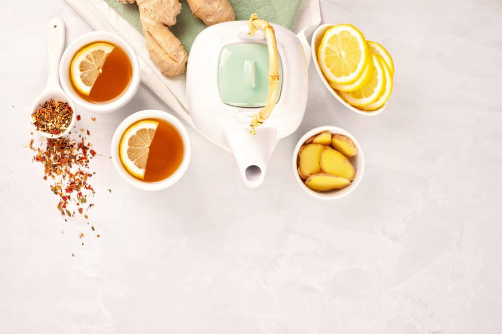 tea pot with tea with lemon, honey, and ginger