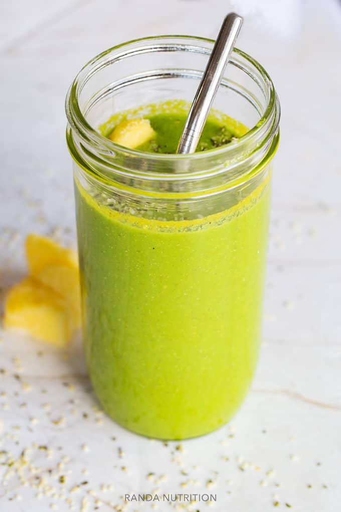 healthy green smoothie with a metal straw in a mason jar