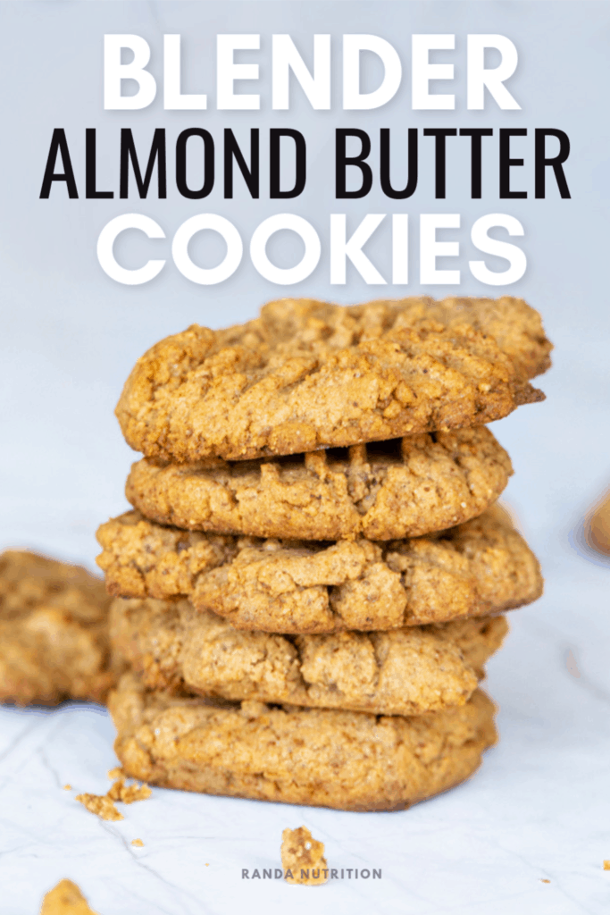 almond butter cookies stacked on top of one another with crumbs