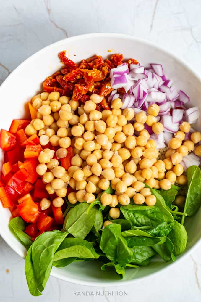 chickpeas, sundried tomatoes, bell peppers, spinach, and onion in a bowl ready to be tossed.