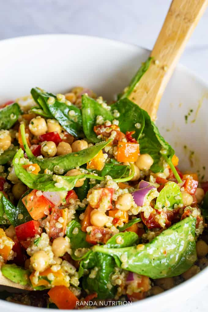Tossing a healthy spinach quinoa salad with a wooden spoon
