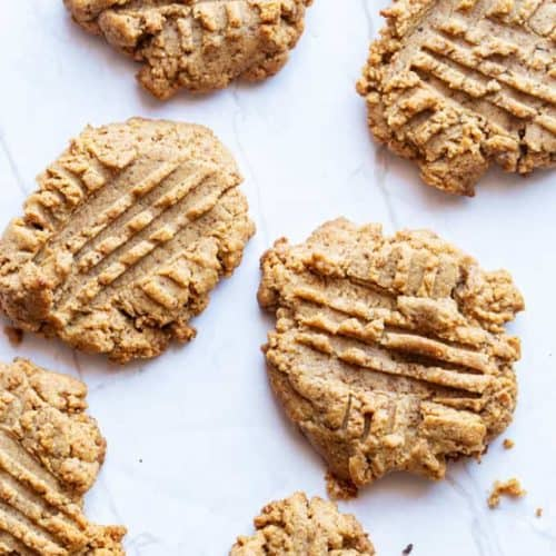 freshly baked almond butter cookies on a marble slab with crumbs