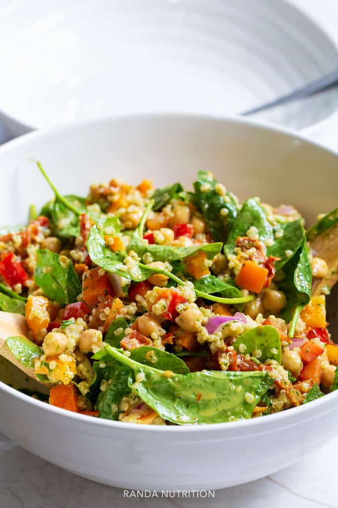 spinach quinoa salad in a white salad bowl