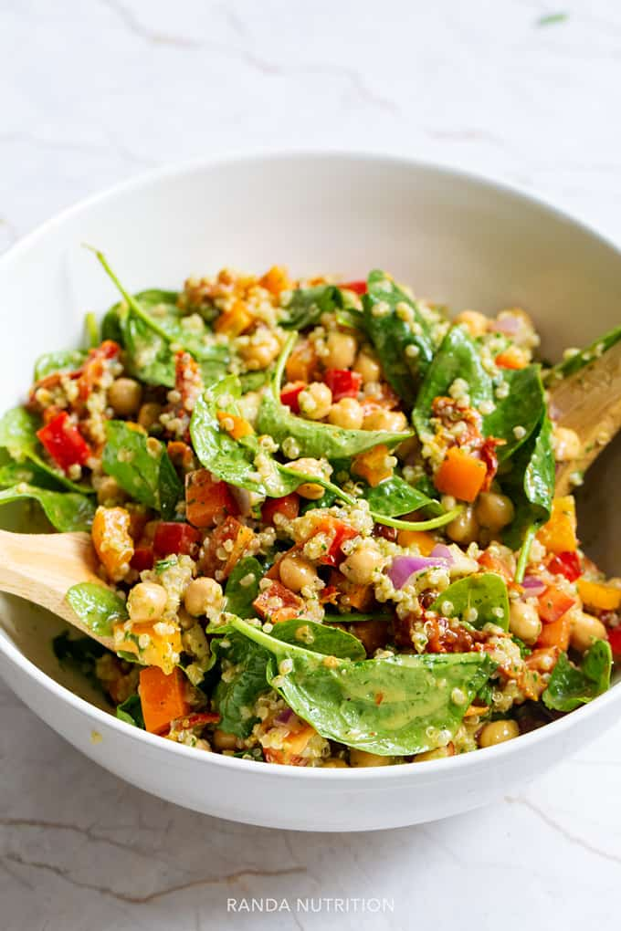 spinach quinoa chickpea salad in a white bowl