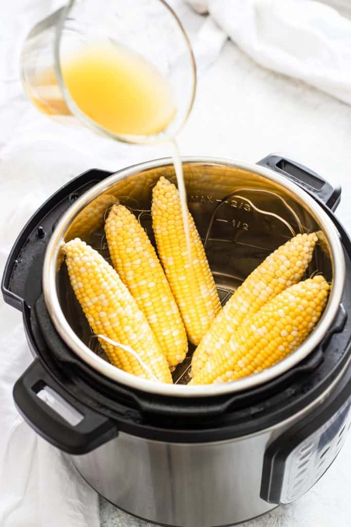 pouring vegetable stock over raw corn in an Instant Pot