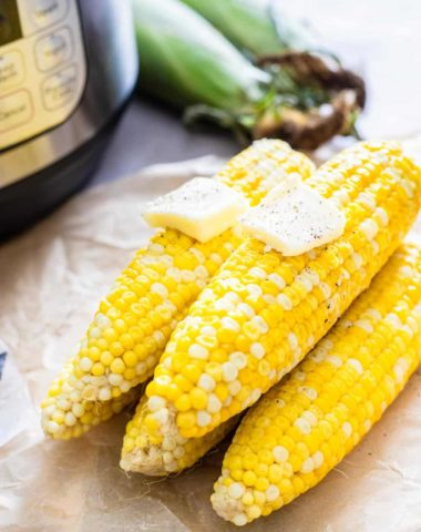 Five corn on the cob stacked on each other with two pats of butter.