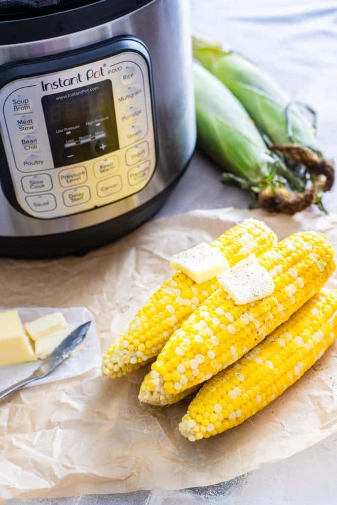 cooked corn next to an instant pot with butter on top