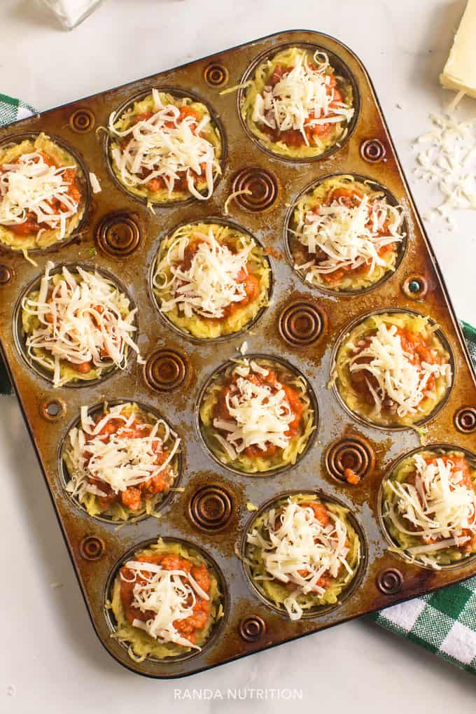 squash, spaghetti sauce, and cheese ready to bake in a muffin tin