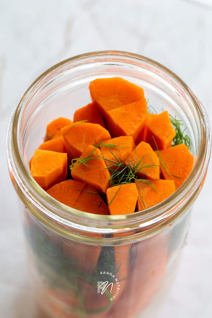 peeled and sliced carrots and dill weed in a mason jar before pickling