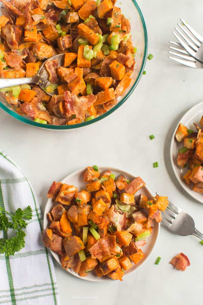 healthy roasted sweet potato salad on a plate with the serving bowl on the top left