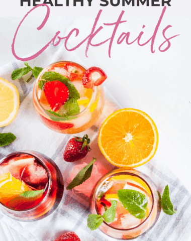 healthy summer cocktails on a white marble background and topped with fruit and mint leaves