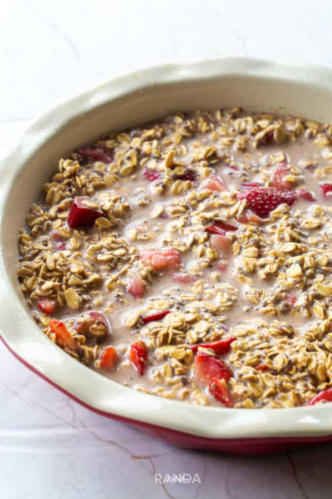 oats, rhubarb, strawberries, and almond milk mixed together and placed in a baking dish about to be placed in the oven