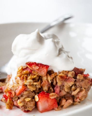 healthy baked oatmeal topped with fruit and coco whip