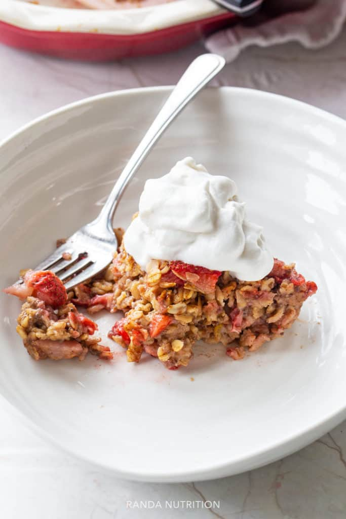 A piece of oatmeal casserole sliced into with a fork, topped with whipped cream