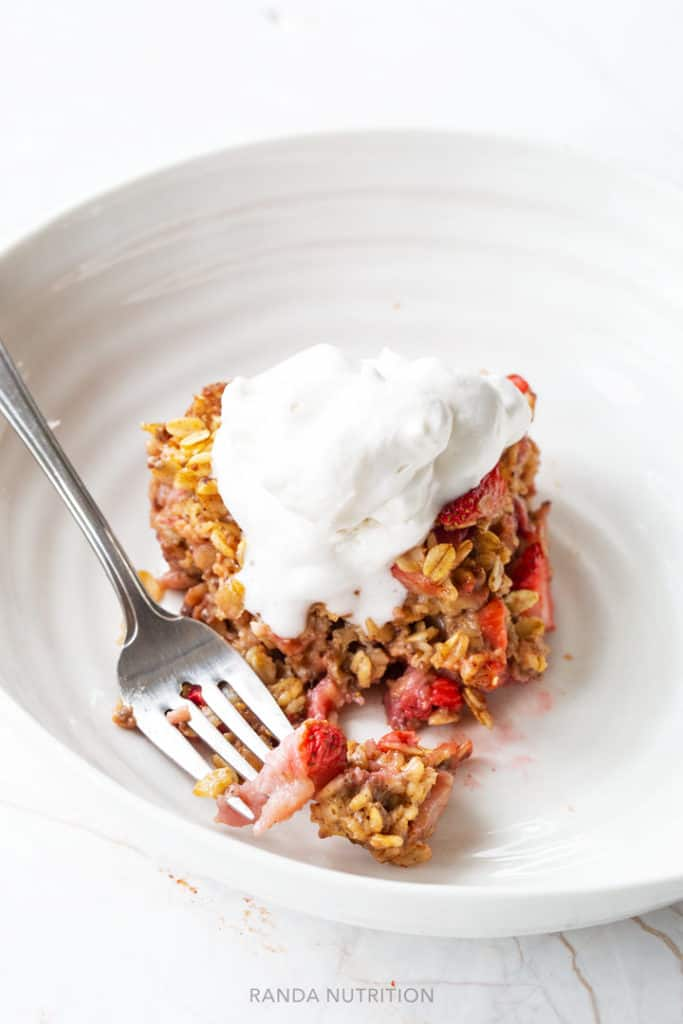 sliced of baked oatmeal stopped with coconut whipped cream