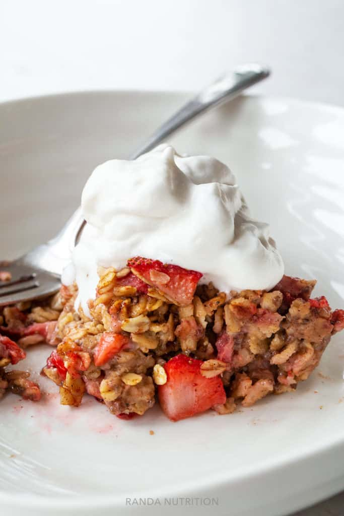 sliced strawberry rhubarb baked oatmeal topped with So Delicious CocoWhip