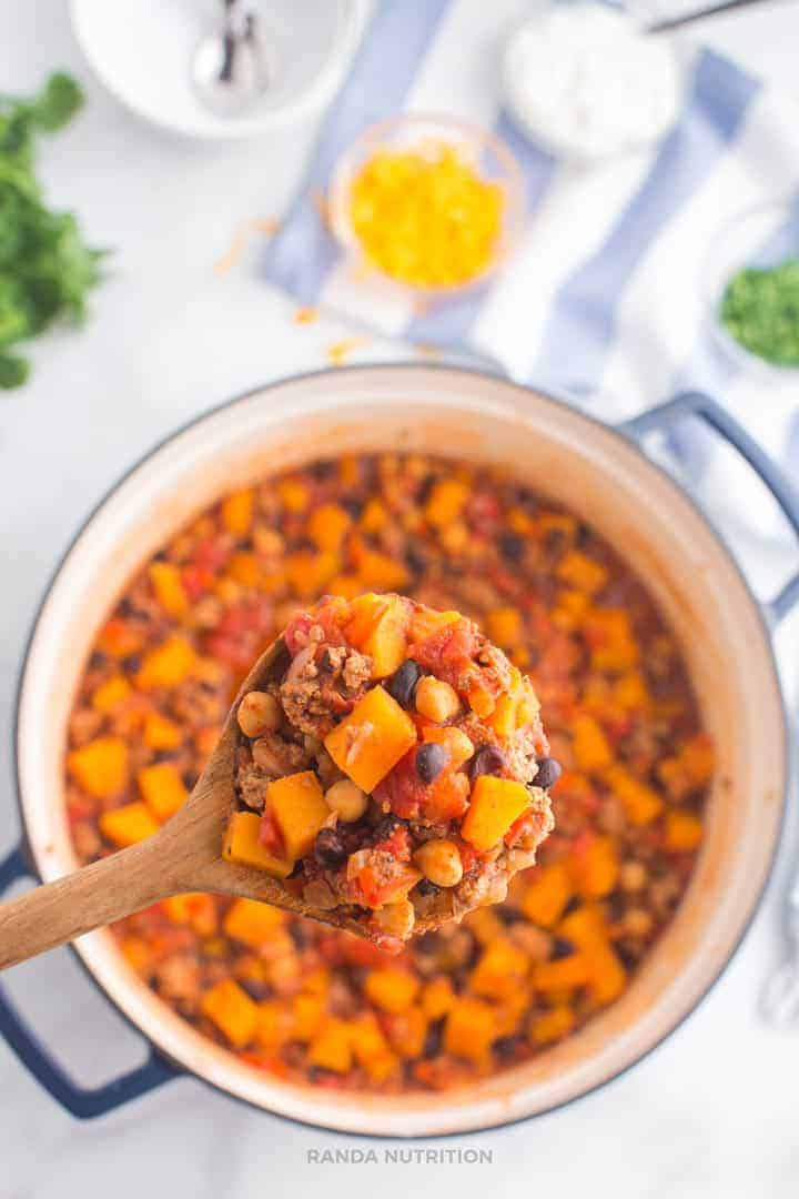 Wooden spoon close up of cooked turkey chili with butternut squash