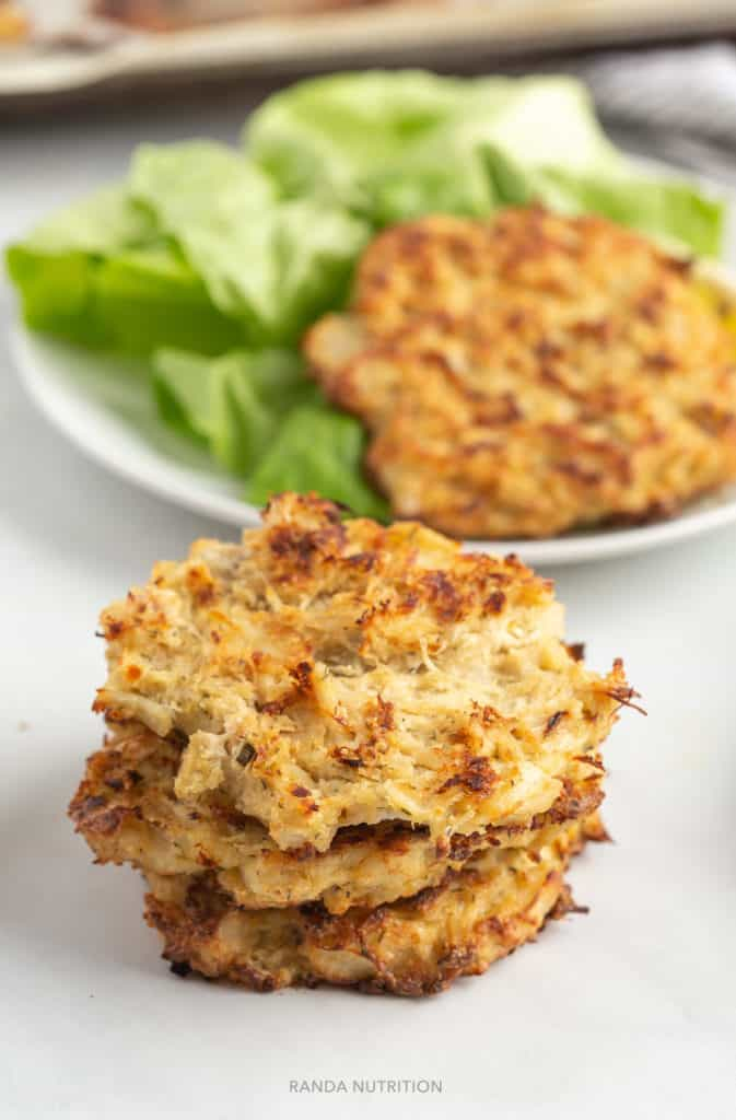 baked crab cakes stacked on top of each other with one on a bed of lettuce in the background