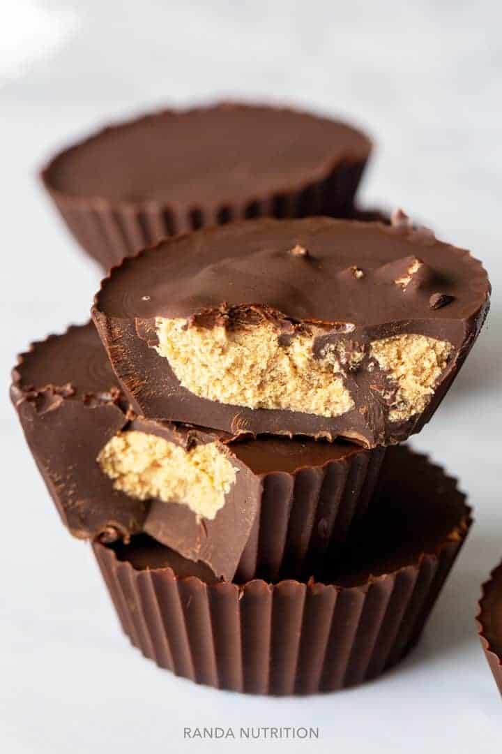 chocolate peanut butter cups stacked on each other with a bite taken out of two showing the protein peanut butter center