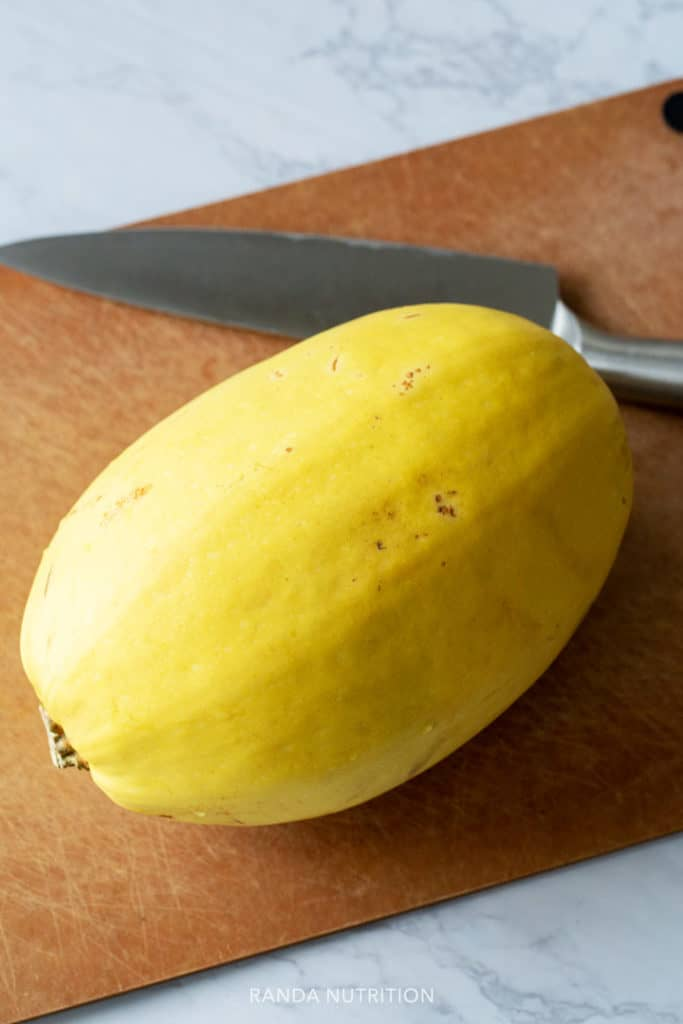 whole spaghetti squash on a cutting board with a knife