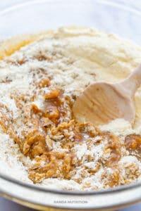 mixing gluten free flour into a pumpkin batter