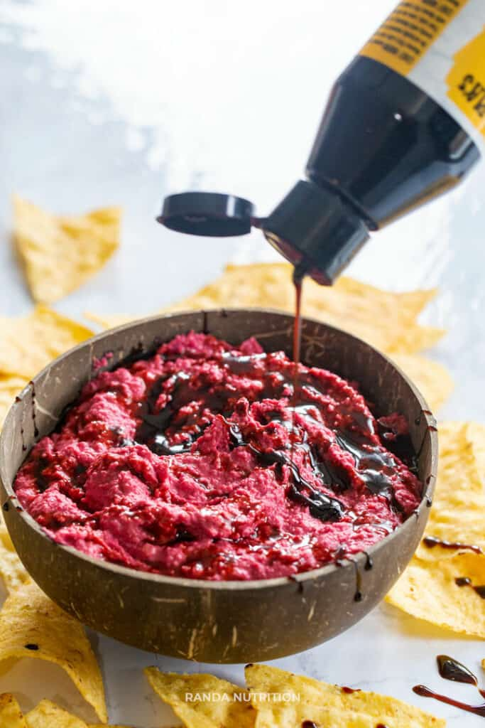 Purple hummus in a coconut shell bowl with balsamic glaze being drizzled over top