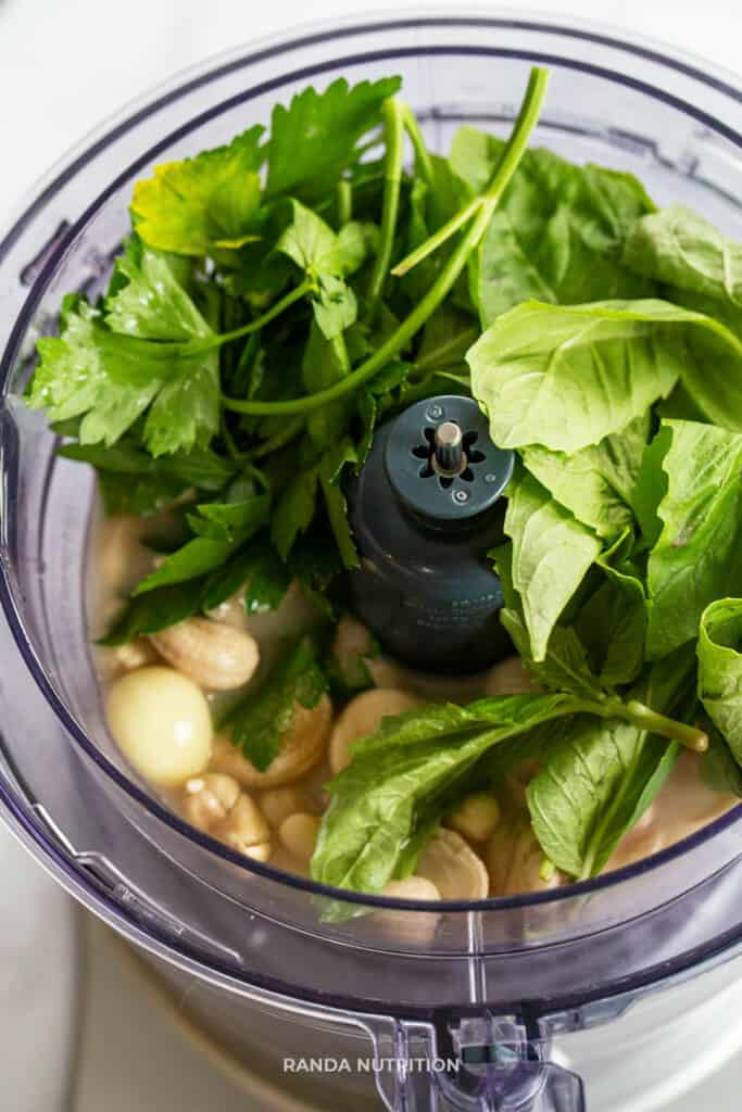 basil, parsley, garlic and cashews about to be blended in a food processor