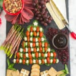 A festive charcuterie board that is simple and easy to make. In shape of a Christmas tree is mozza balls, tomatoes over spinach. Includes a bowl of mixed nuts, grapes, sliced brie cheese, and crackers in the shape of presents.