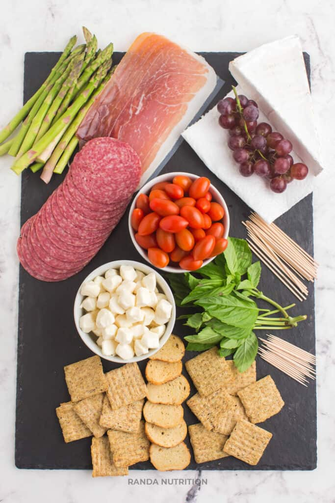 easy charcuterie board ingredients include prosciutto, crackers, balsamic glaze, grapes, herbs, mozza balls, tomatoes, brie, and more