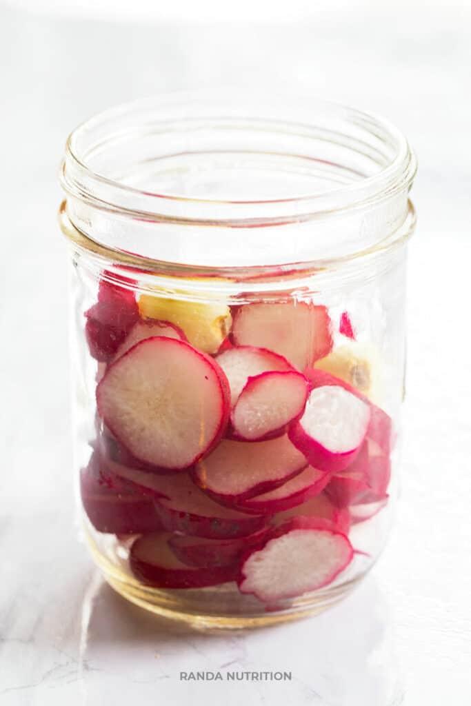radishes in a clean mason jar with garlic