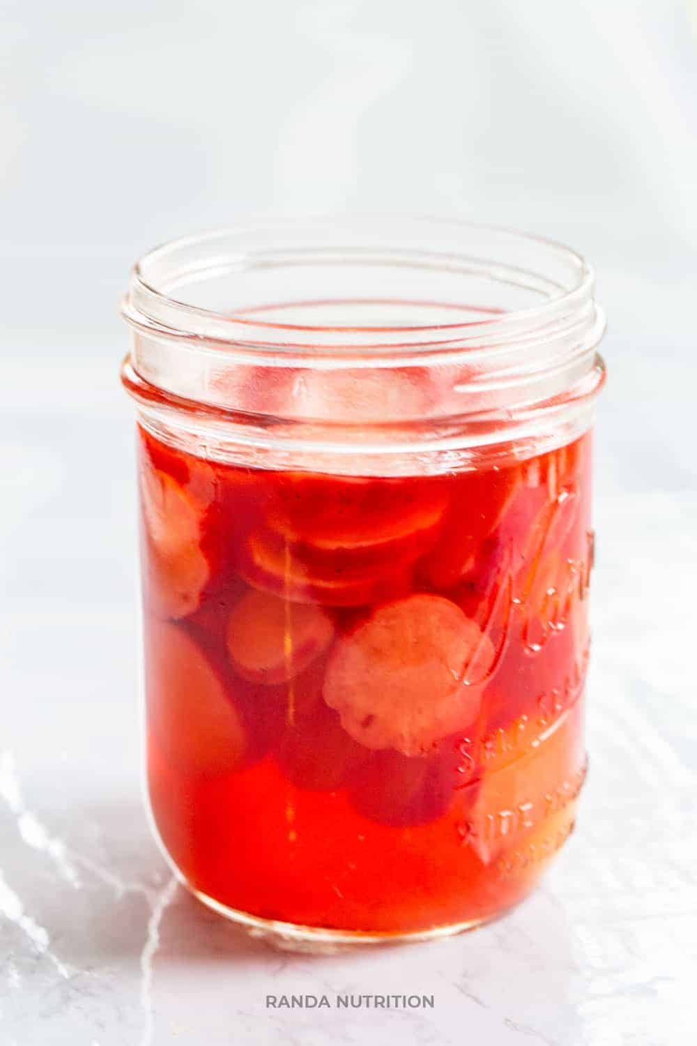 pickled radishes in a mason jar with apple cider vinegar