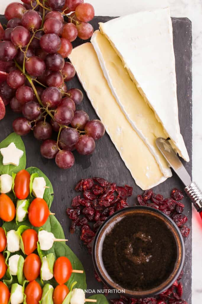 brie, grapes, and balsamic glaze on a slate for appetizersThis simple DIY Christmas Tree Caprese Board is such an easy idea! If you're wondering how to make a charcuterie board that will appeal to a crowd (keto, healthy, and vegetarian) this holiday meat and cheese platter has something for every lifestyle. Added mozzarella, tomatoes, and basil for a cheese board that will be the best Christmas party appetizer ideas! #charcuterieboard #capreseboard #christmasparty