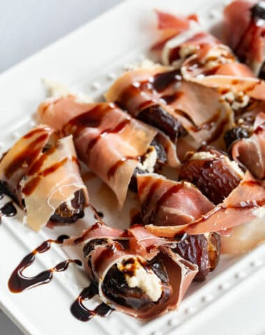 stuffed dates with a balsamic reduction drizzled over top of a white platter
