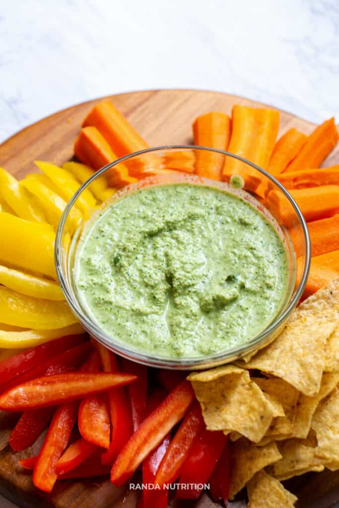 vegan dip with herbs served on a platter of veggies