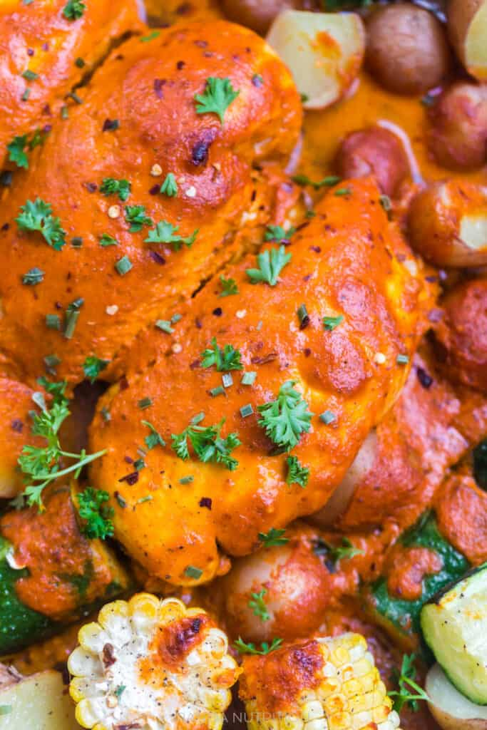 close up of baked chicken with a red pepper sauce on top