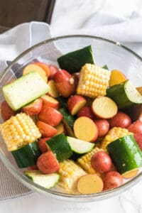 corn, zucchini, and baby red potatoes in a bowl with olive oil and salt and pepper